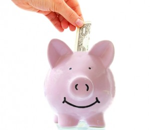 smiling pink piggy bank with hand saving money